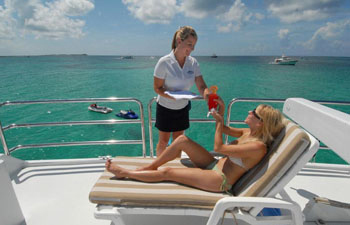 Served a cocktail while sunbathing on crewed yacht charter.